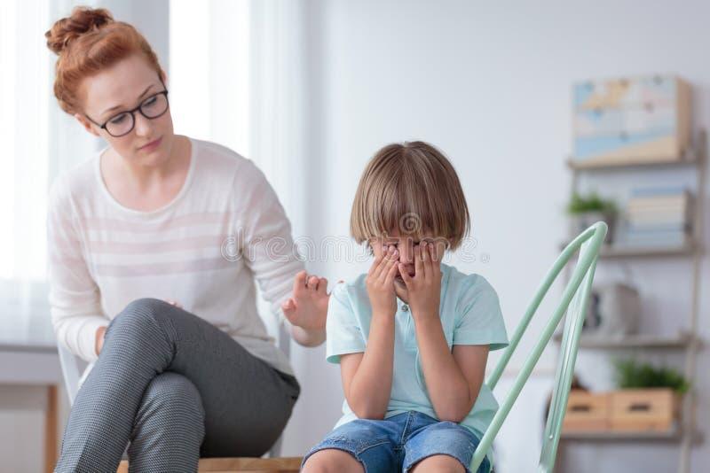 Mère inquiétée soulageant le fils pleurant photos libres de droits