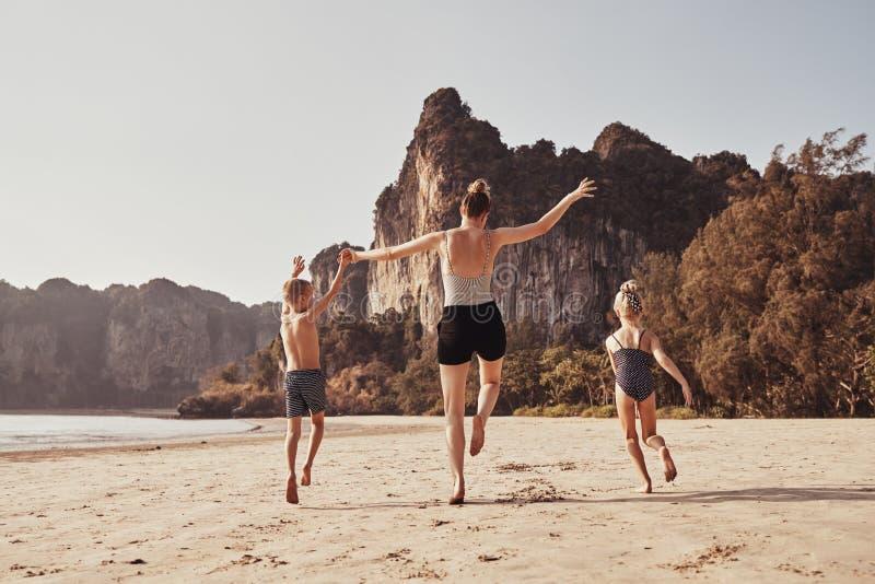 Mère insouciante et enfants courant le long d'un togethe de plage sablonneuse photo stock