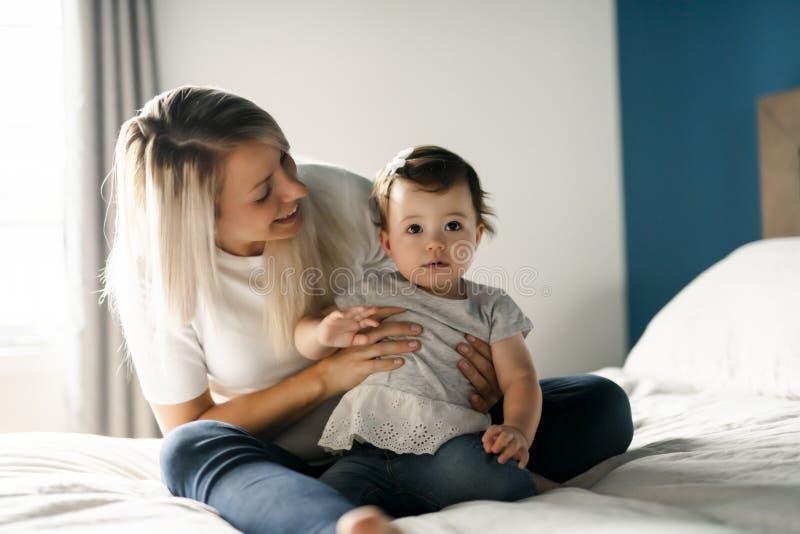 Mère jouant avec la fille de bébé dans la chambre à coucher à la maison photo libre de droits