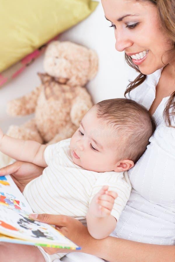 Mère joyeuse affichant un livre à sa chéri photo stock
