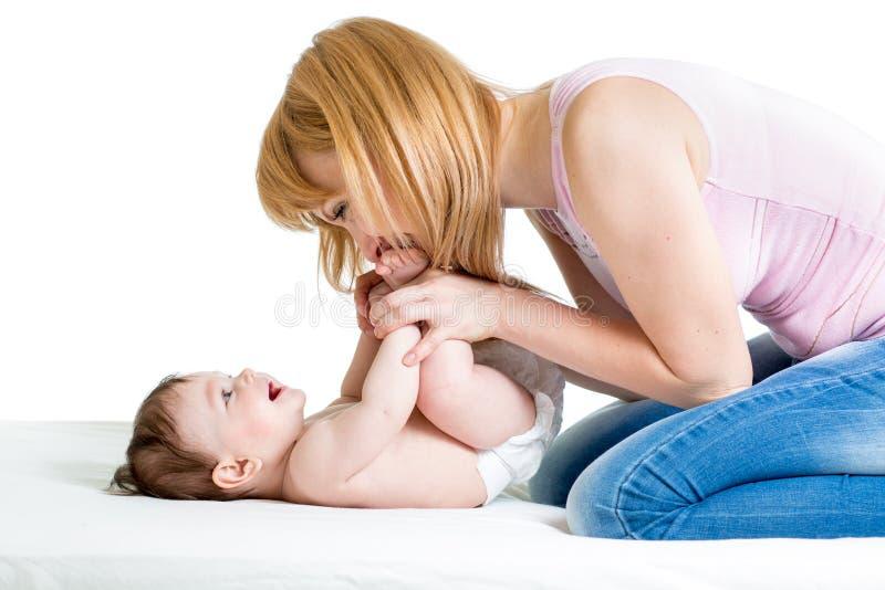 Mère joyeuse jouant avec le nourrisson de bébé photographie stock