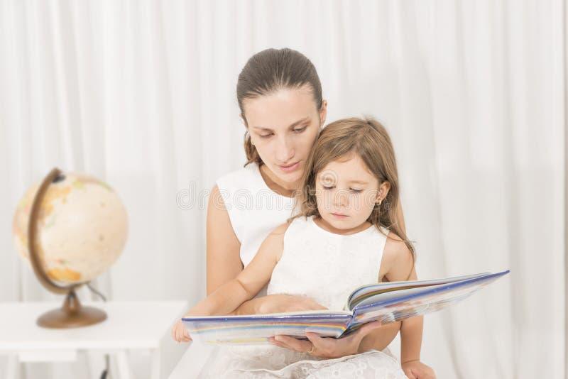 Mère lisant un livre à son enfant image stock