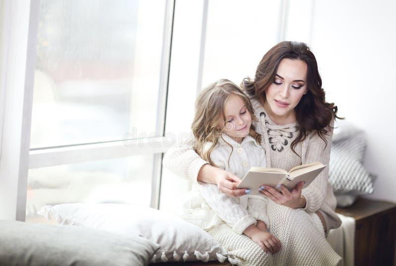 Mère lisant un livre à une fille photos stock