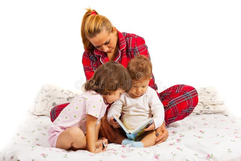 Mère lisant une histoire pour endormir à ses enfants photographie stock