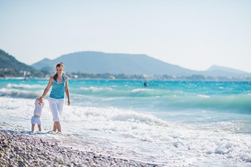 Mère marchant avec la chéri sur le bord de la mer photos libres de droits