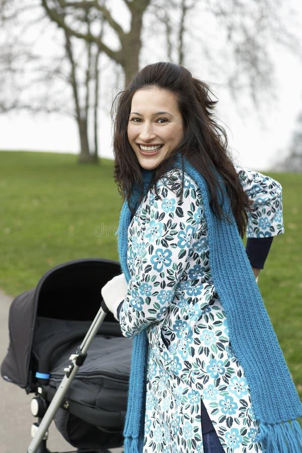 Mère marchant avec la voiture d'enfant en parc photos stock