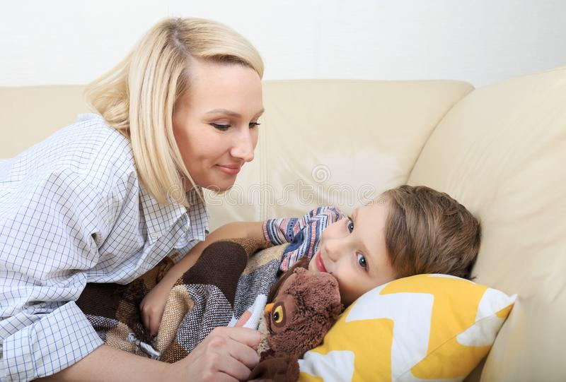 Mère mettant le fils pour dormir Mère mettant le fils pour enfoncer Enfant de sommeil doux avec la belle maman photo libre de droits