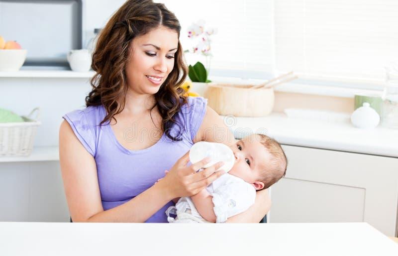 Mère mignonne alimentant sa chéri dans la cuisine photo libre de droits