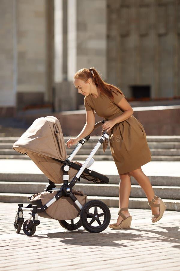 Mère moderne à la mode sur une rue de ville avec un landau. Jeune mère photo libre de droits