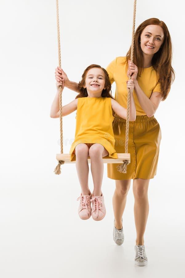 Mère montant la petite fille heureuse sur l'oscillation photos stock