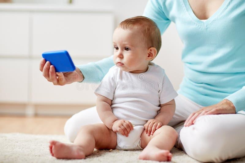 Mère montrant le smartphone au bébé à la maison images libres de droits