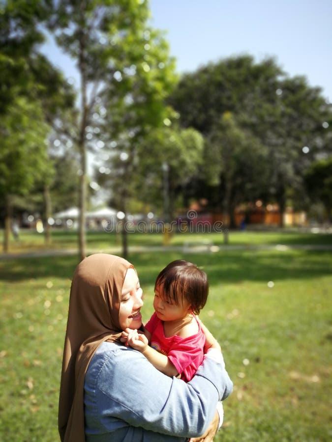 Mère musulmane portant et jouant avec son bébé en parc photographie stock