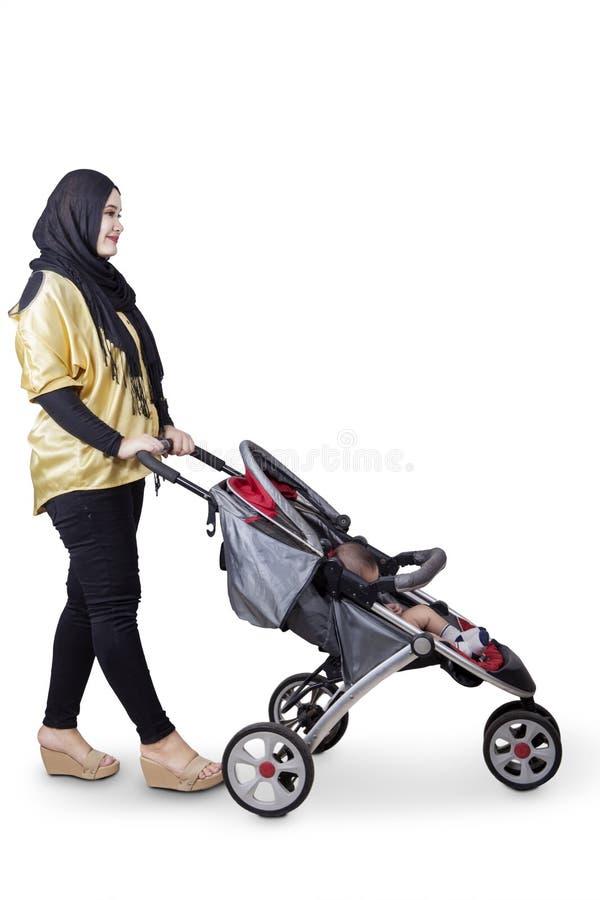 Mère musulmane poussant la poussette de bébé image libre de droits