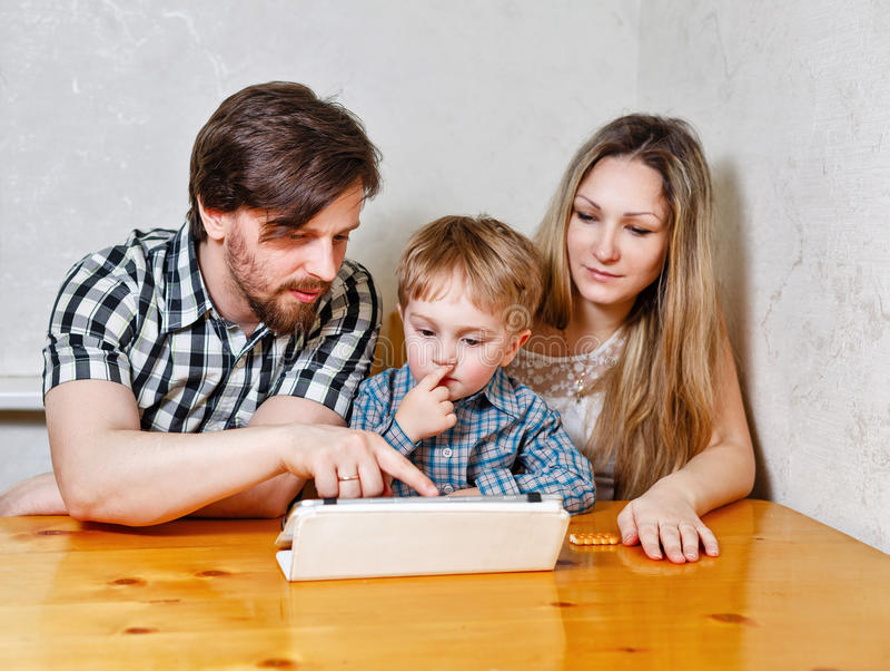 Mère, père et fils de famille regardant le PC de comprimé photos stock