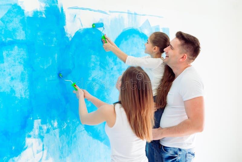 Mère, père et petite fille peignant le mur dans leur nouvelle maison photographie stock