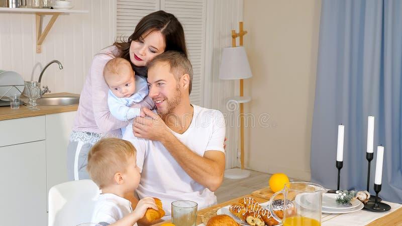 Mère, père heureux et fils prenant le petit déjeuner à la maison image stock