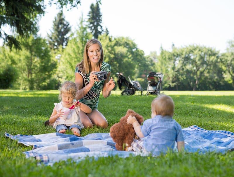 Mère photographiant des enfants en parc image stock