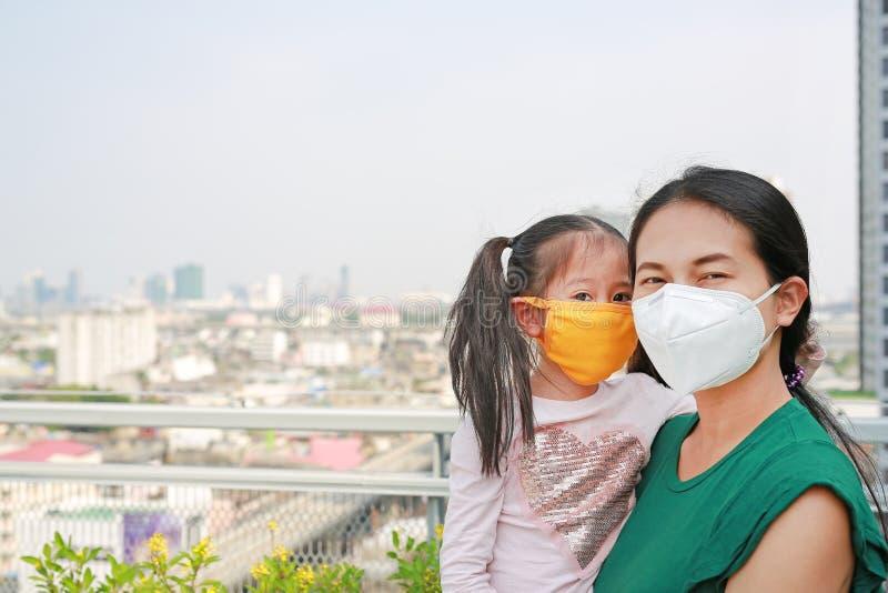 Mère portant sa fille avec porter un masque de protection contre P.M. 2 pollution 5 atmosph?rique dans la ville de Bangkok thaila photo stock