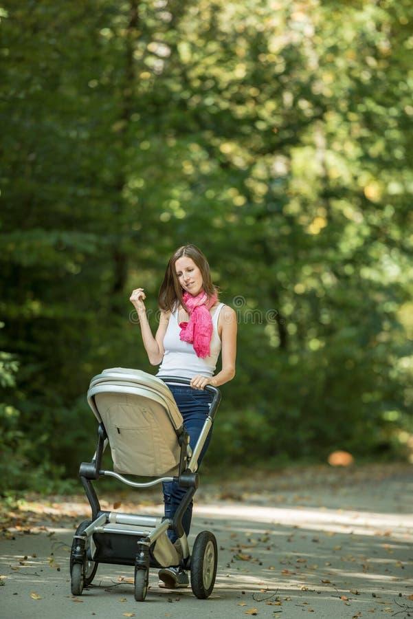 Mère poussant la voiture d'enfant en parc images stock