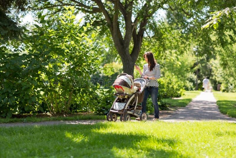 Mère poussant la voiture d'enfant en parc photos stock