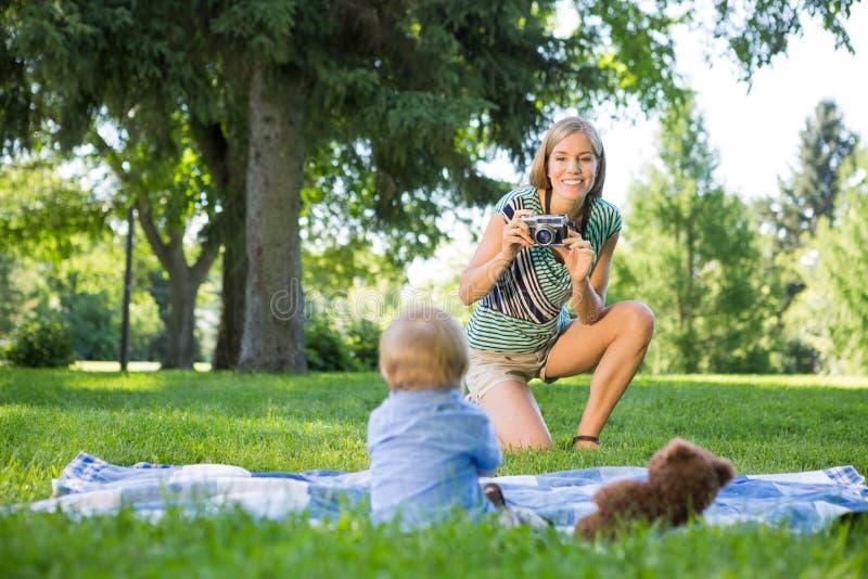 Mère prenant la photo du bébé garçon en parc photographie stock libre de droits