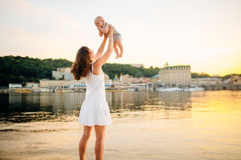 Mère qui tourne l'enfant contre un coucher du soleil et une eau Maman et ch?ri heureuses Jouer sur la plage Jeune femme jetant en photos libres de droits