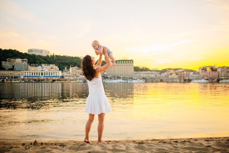 Mère qui tourne l'enfant contre un coucher du soleil et une eau Maman et ch?ri heureuses Jouer sur la plage Jeune femme jetant en image stock