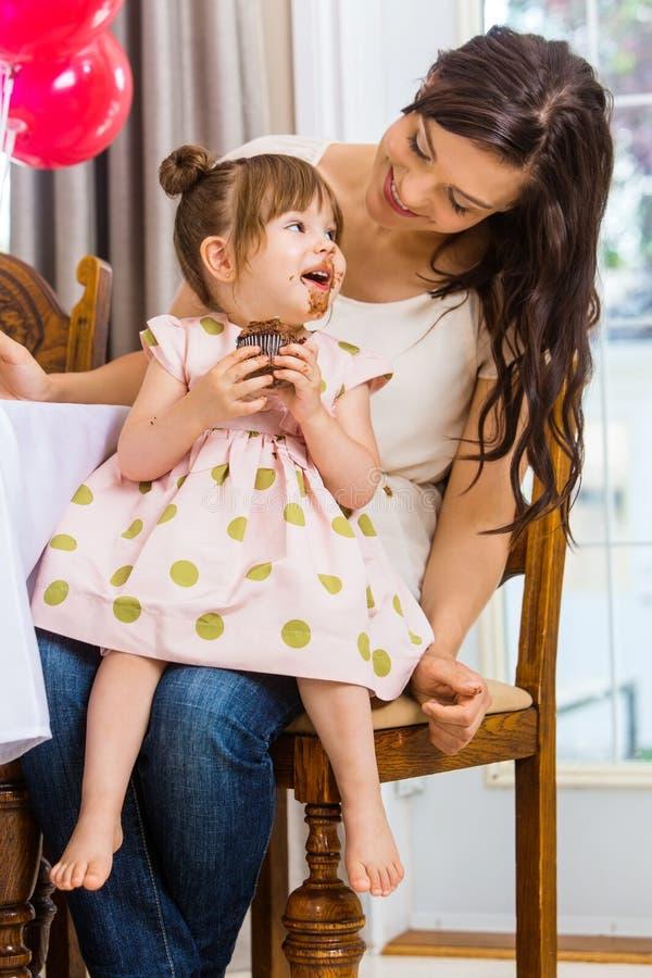 Mère regardant la fille d'anniversaire mangeant le petit gâteau photos stock