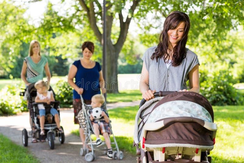 Mère regardant le bébé dans la poussette le parc image stock