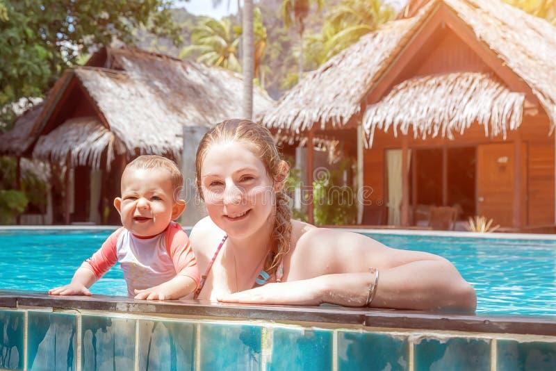 Mère riante heureuse avec la fille huit mois dans la piscine Ils sourient et ont l'amusement des vacances d'été Pavillons en bois images libres de droits