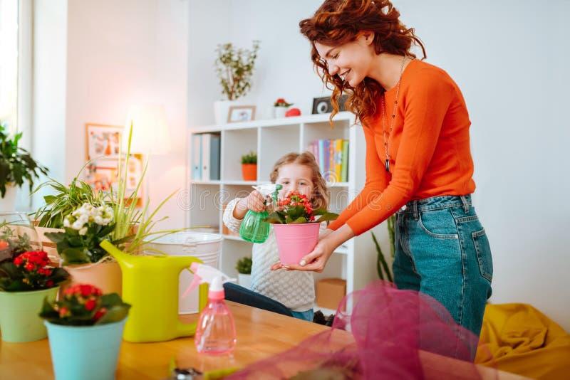 Mère rousse sentant les fleurs de arrosage heureuses avec la fille photographie stock