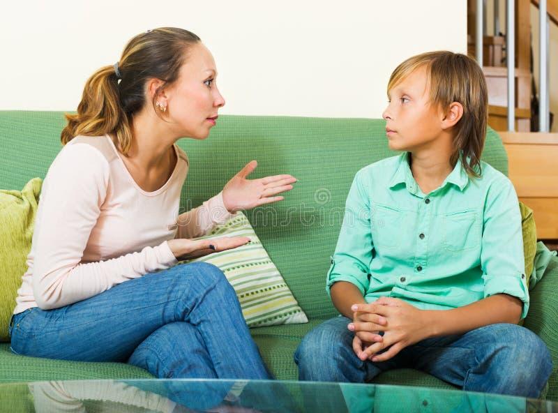 Mère sérieuse et garçon d'ado parlant dans la maison photo libre de droits