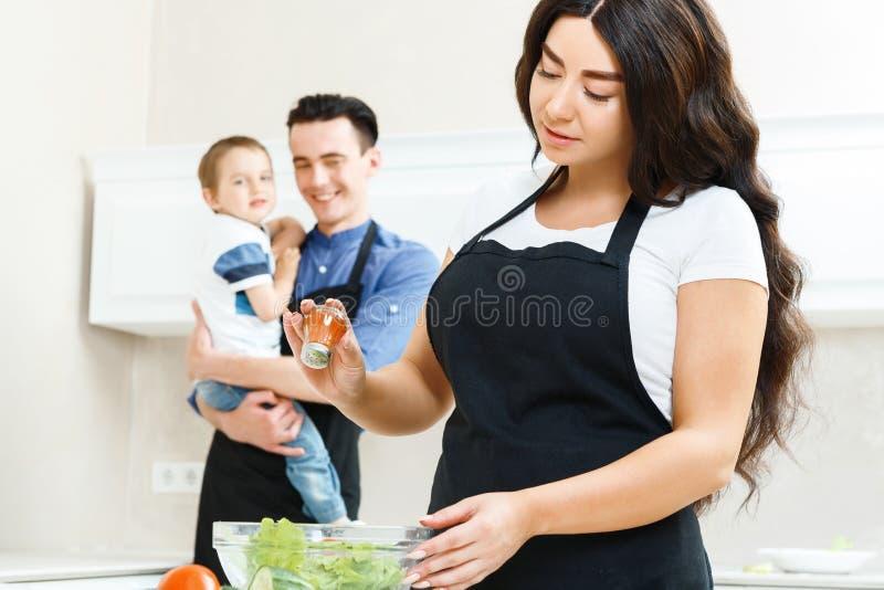 Mère salant la salade dans la cuisine images stock