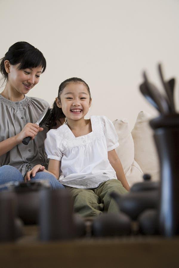 Mère se brossant les cheveux de filles image stock