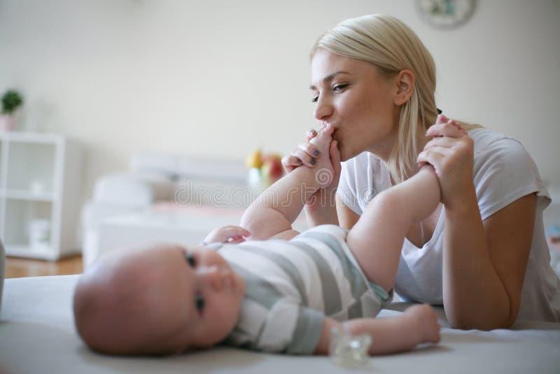 Mère souriante jouant avec son bébé garçon à la maison images stock