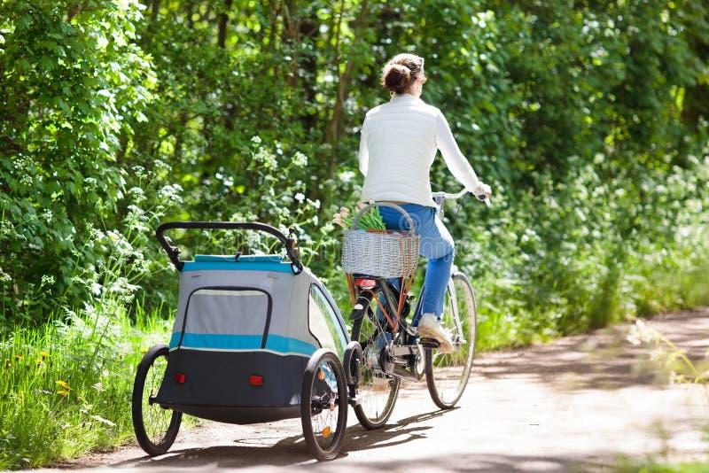 Mère sur la bicyclette avec la remorque de vélo de bébé en parc image stock