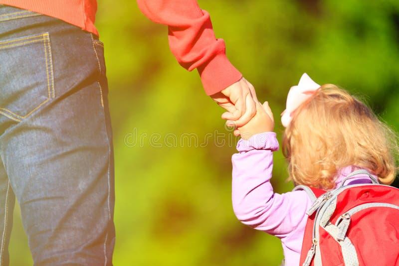 Mère tenant la main de la petite fille dehors photos stock