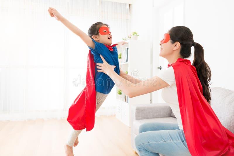 Mère tenant la petite fille mignonne faisant la pose de mouche photographie stock libre de droits