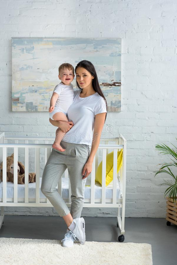 mère tenant le bébé de sourire mignon dans des mains tout en se tenant à la huche de bébé photos libres de droits