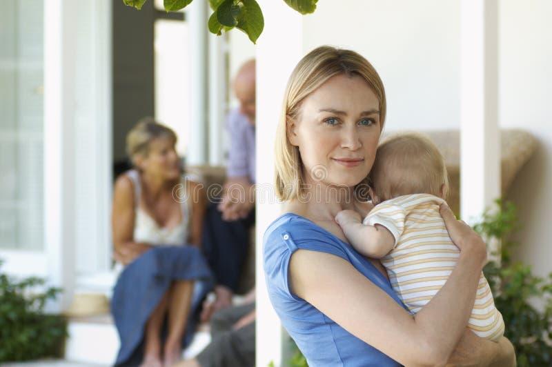 Mère tenant le bébé sur le porche avec des grands-parents derrière photos stock