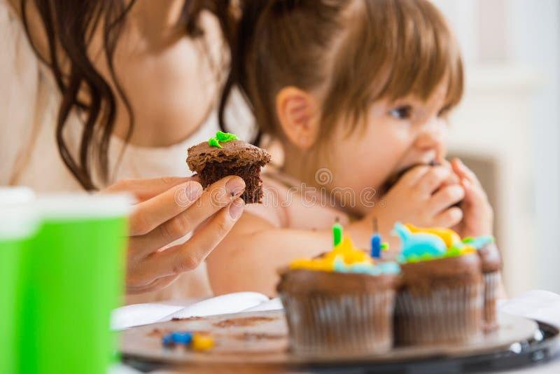 Mère tenant le petit gâteau avec la fille mangeant le gâteau photo stock