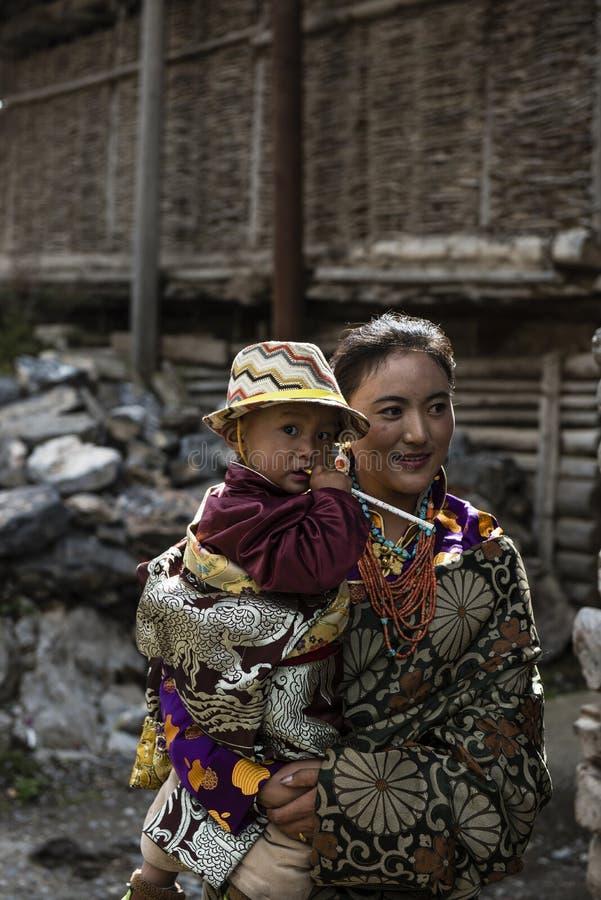 Mère tibétaine tenant son fils au soleil photographie stock libre de droits