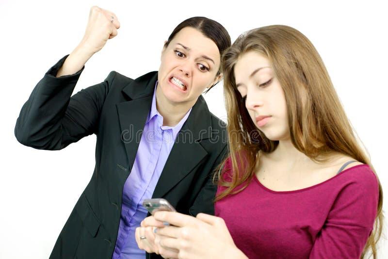 Mère voulant détruire le téléphone portable de la fille photo stock
