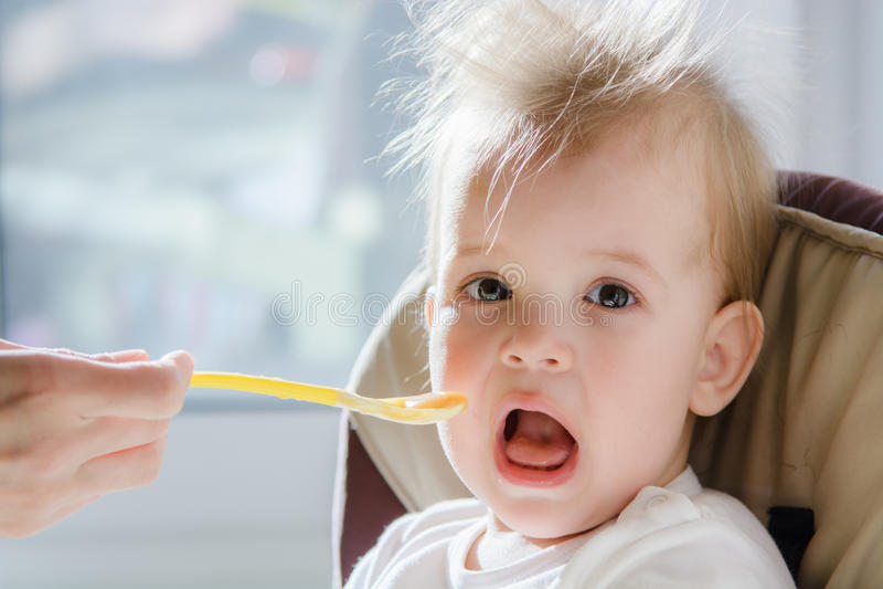 Mères alimentant le bébé avec le fromage blanc image stock