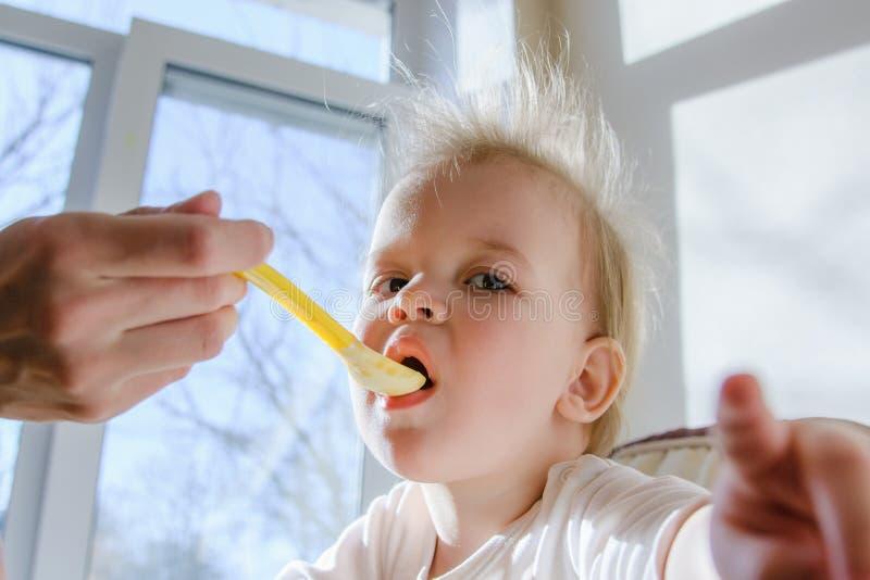 Mères alimentant le bébé avec le fromage blanc images stock