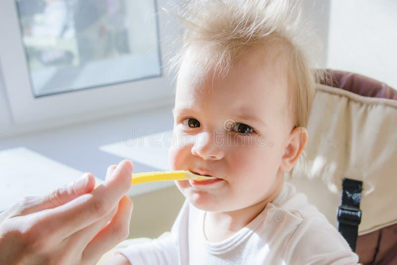 Mères alimentant le bébé avec le fromage blanc photographie stock libre de droits