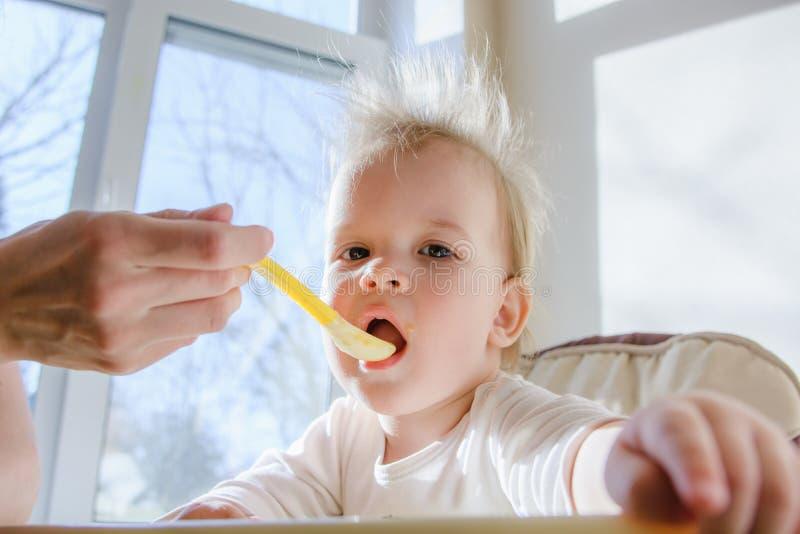 Mères alimentant le bébé avec le fromage blanc images libres de droits