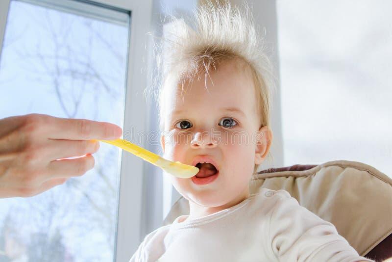 Mères alimentant le bébé avec le fromage blanc image libre de droits