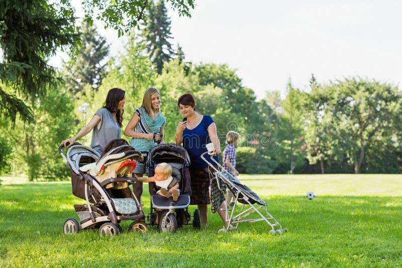 Mères avec des promeneurs de bébé lisant le message textuel images libres de droits