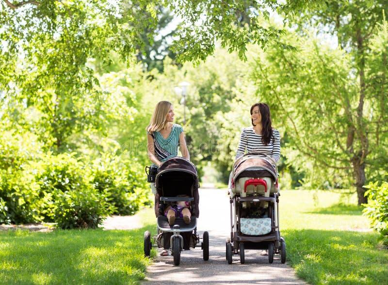 Mères avec des voitures d'enfant marchant en parc images stock